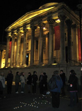 people gather in Trafalgar Square with candles, National Gallery in background, photo by Sarah Barnes