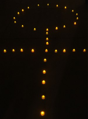 candles arranged in woman symbol at trafalgar square, London, photo by Ange